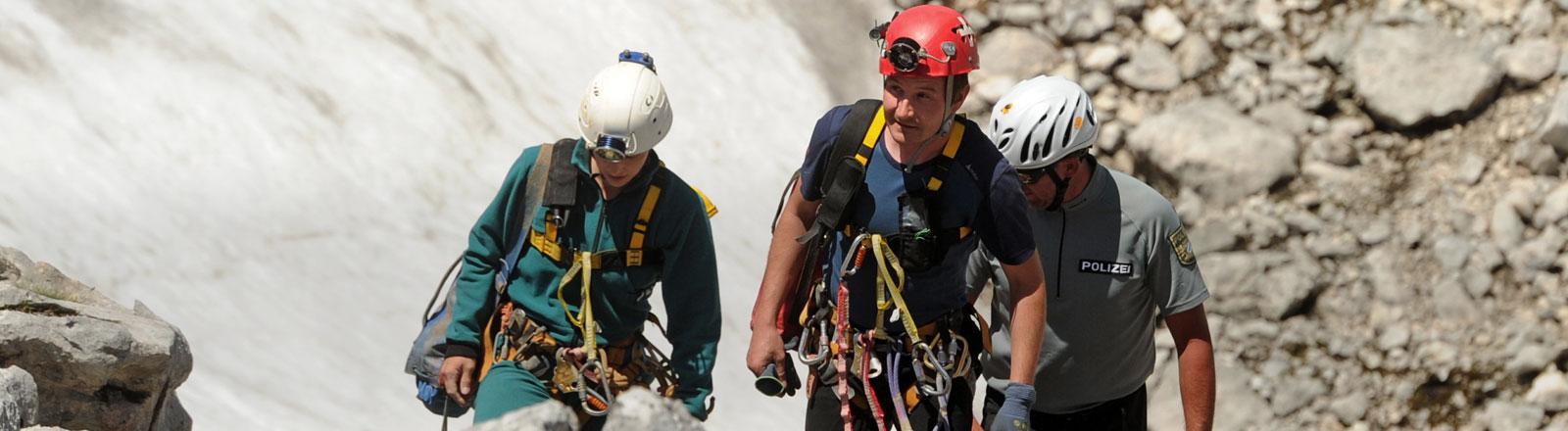Auf Höhlenrettungen spezialisierte Helfer aus der Schweiz, die kurz zuvor mit dem Hubschrauber gebracht wurden, kommen am 10.06.2014 am Untersberg bei Marktschellenberg (Bayern) zum Eingang der Riesending-Schachthöhle.