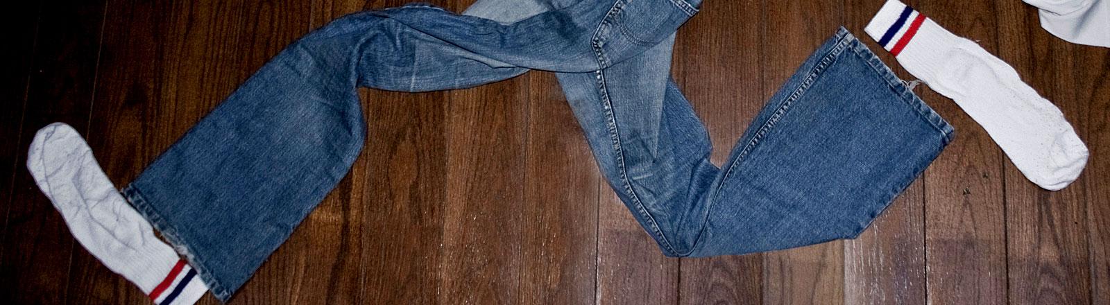 Eine Stonewashed-Jeans mit weißen Socken.