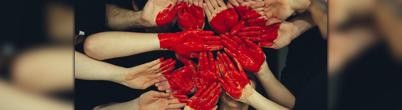 Viele Hände zeigen in die Kamera auf die ein großes rotes Herz gemalt ist