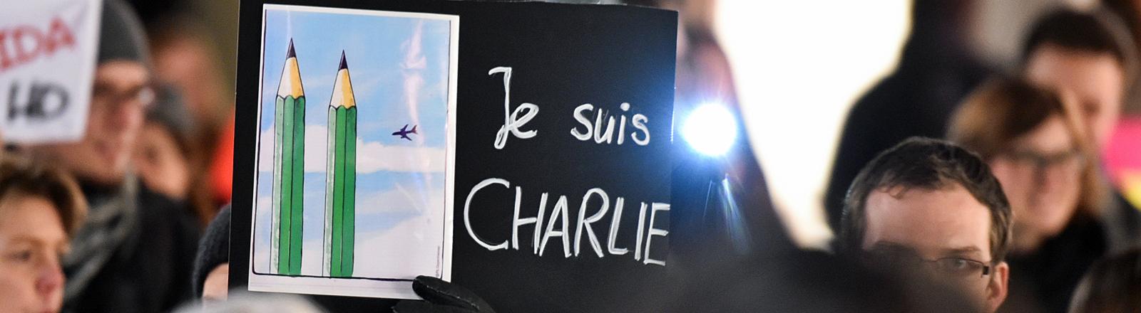 """Teilnehmer der Initiative """"NOGIDA"""" halten am 12.01.2015 in Heidelberg bei einer Kundgebung in der Innenstadt ein Plakat mit einer Karikatur und der Aufschrift """"Je suis Charlie"""" in die Höhe."""