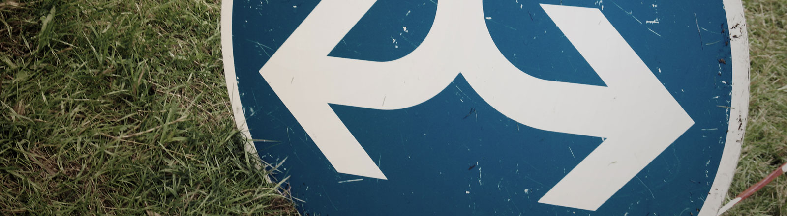Ein Straßenschild mit Pfeilen, die in zwei Richtungen zeigen.