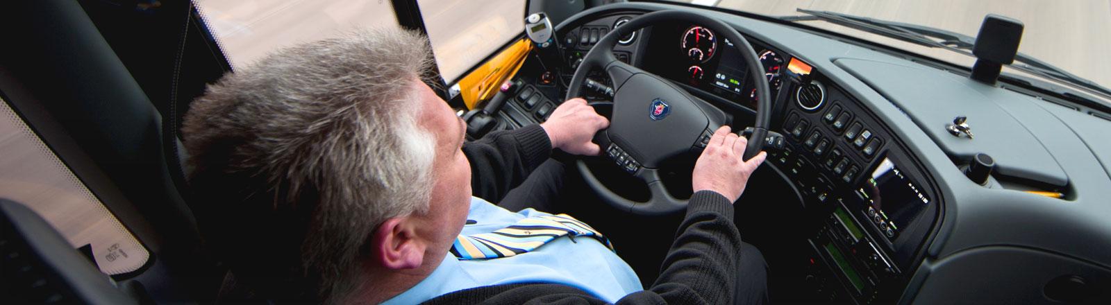 Ein Busfahrer am Steuer eines ADAC-Postbusses.