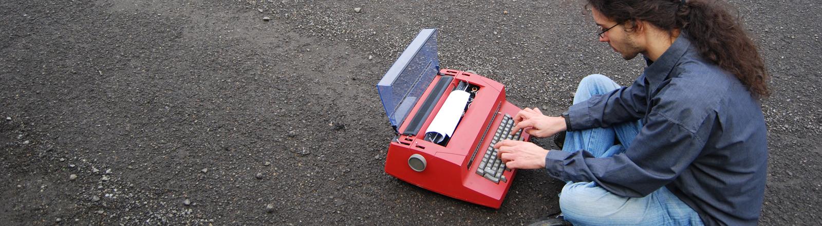 Ein Mann mit Zopf sitzt auf einer Schotterstraße und tippt in eine rote Schreibmaschine.