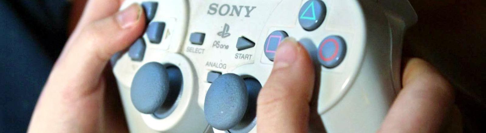 Junge spielt mit einer Playstation1.
