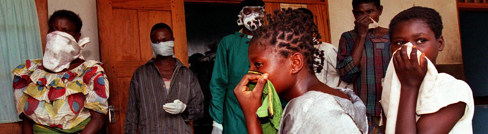 Angehörige von Patienten, die sich mit dem Ebola-Virus infiziert haben, warten vor einem Krankenhaus auf Neuigkeiten.