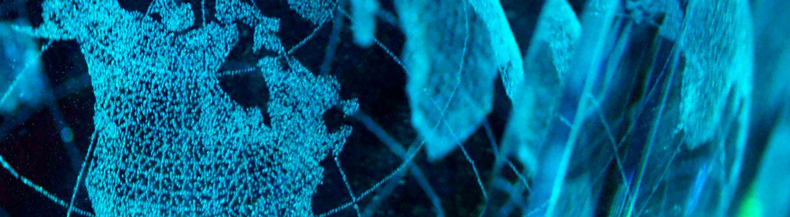 Eine stilisierte Erdkugel schimmert im digitalen Blau.