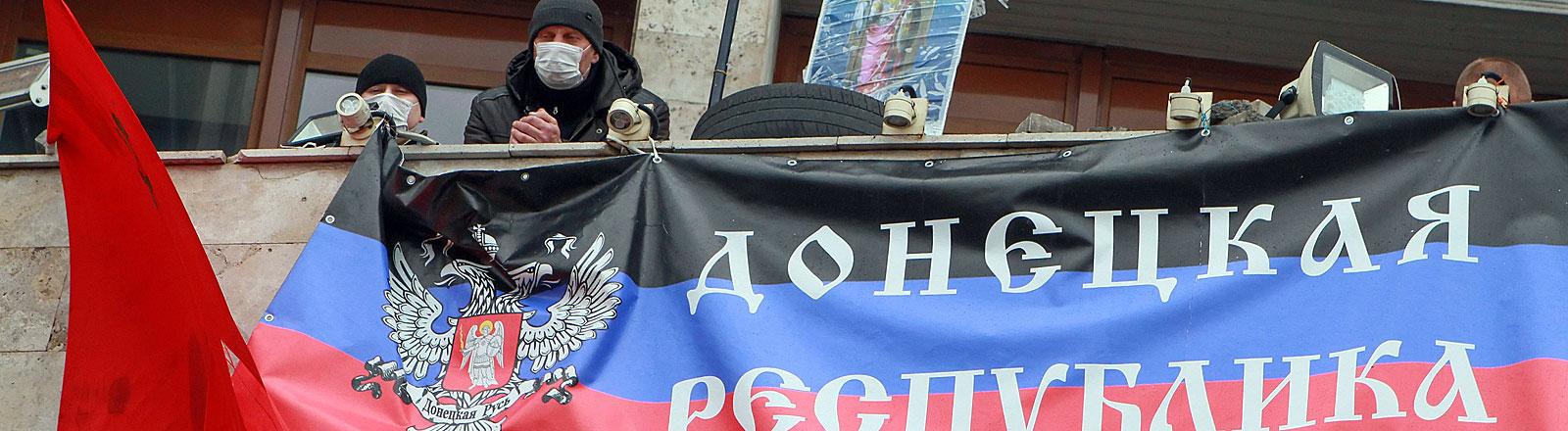 """14.April 2014: Pro-Russische Demonstranten haben am Balkon der Regionaladministration in Donezk ein Banner mit der Aufschrift """"Republik Donezk"""" gehisst."""