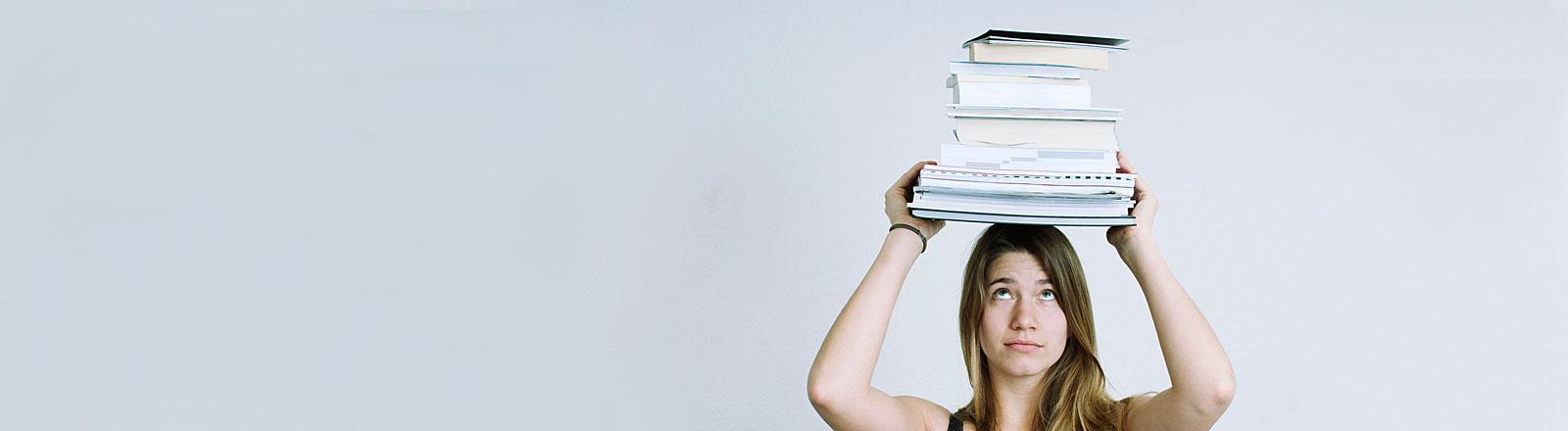 Eine Studentin mit Büchern auf dem Kopf balancierend