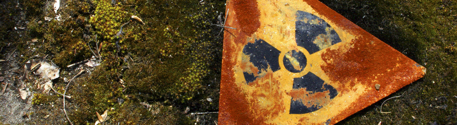 Auf dem Boden bei Tschernobyl liegt ein altes Schild, dass vor radioaktiver Strahlung warnt.