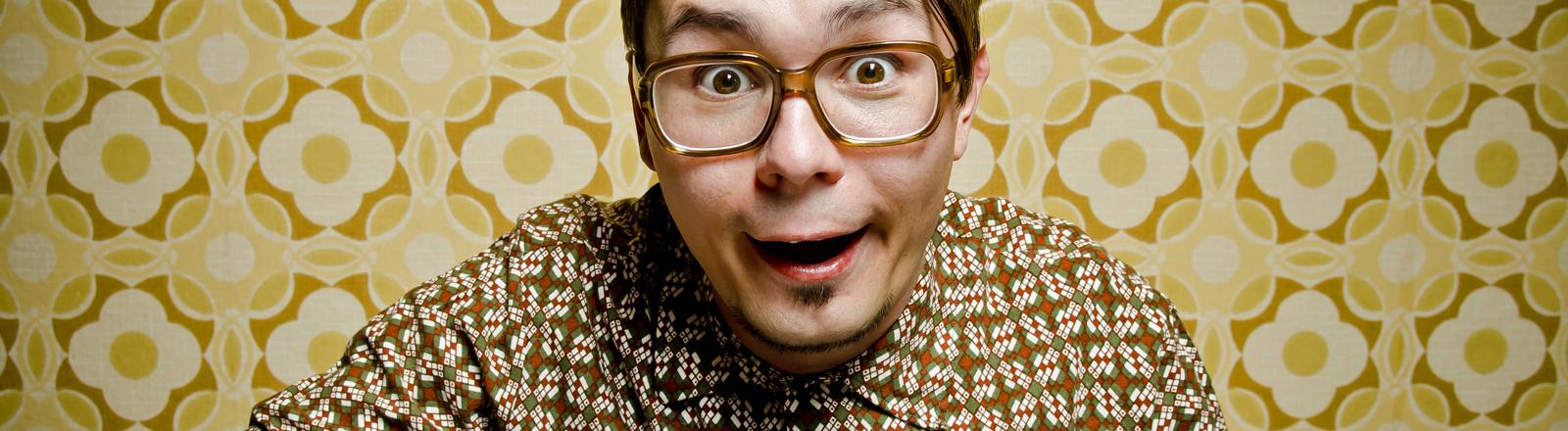 Ein Retro-Nerd mit großer Brille und Seitenscheitel tippt begeistert in eine Tastatur.