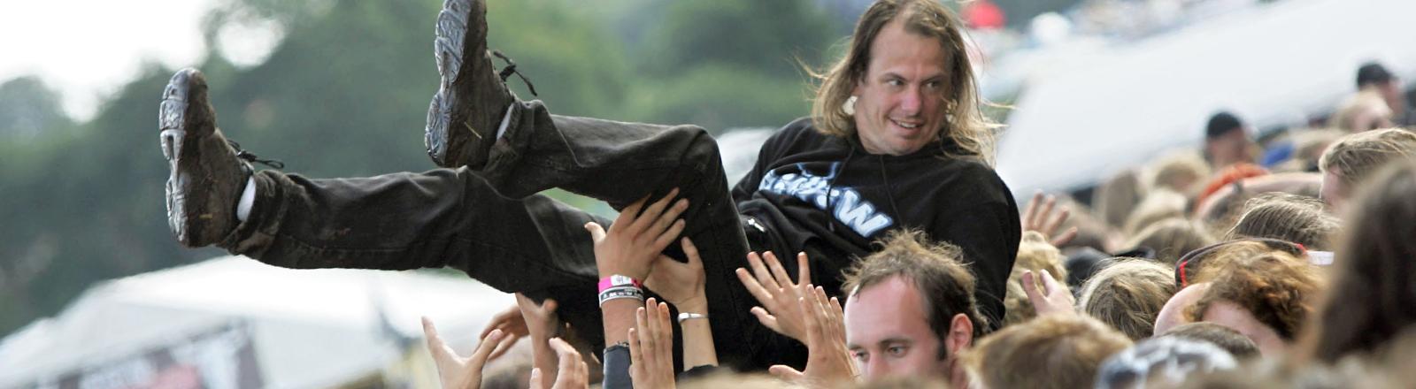 Ein Besucher des Wacken Open Air Festivals wird auf dem Festivalgelände vor der Bühne über die Menge getragen.