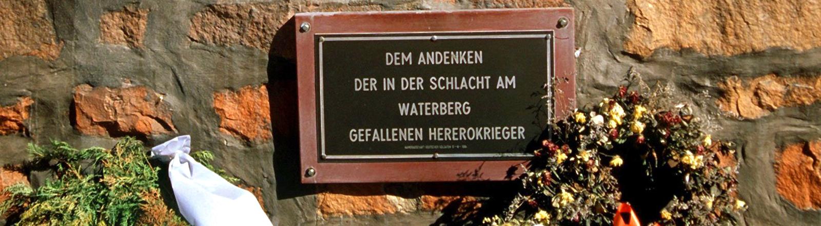 Eine mit Kränzen geschmückte Gedenktafel auf dem deutschen Friedhof am Waterberg (Nambia) für die Herero-Krieger, die bei der entscheidenden Schlacht am 11. August 1904 gegen die deutschen Kolonialtruppen gefallen sind