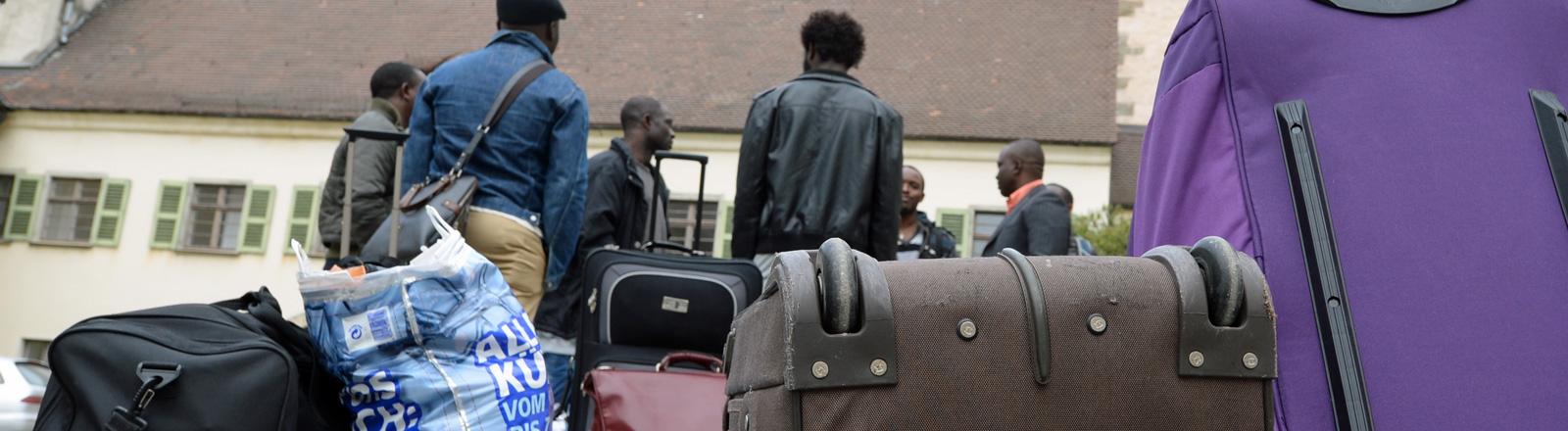 Mehrere Flüchtlinge stehen am 03.04.2014 in Weingarten (Baden-Württemberg) nach ihrer Ankunft vor dem Gästehaus des Klosters Weingarten.