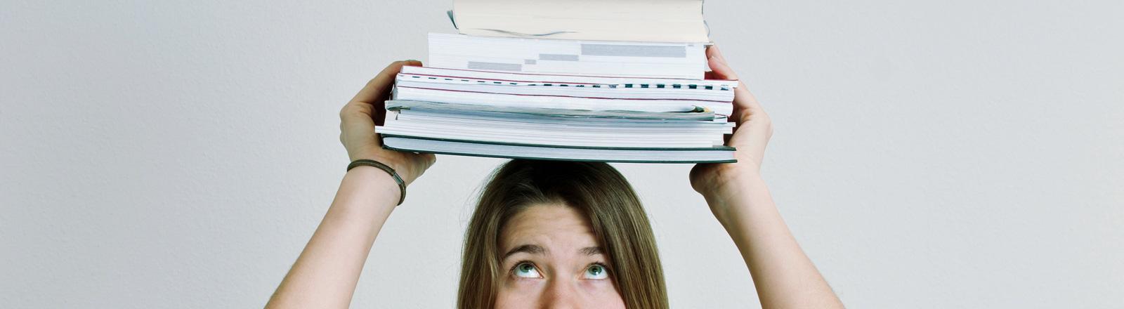 Eine junge Frau trägt einen Stapel Unterlagen auf dem Kopf.