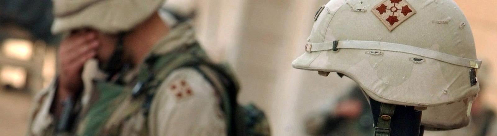 Ein US-Soldat trauert um zwei gefallene Kameraden. Ihre Helme sind auf ihre Waffen gesteckt.