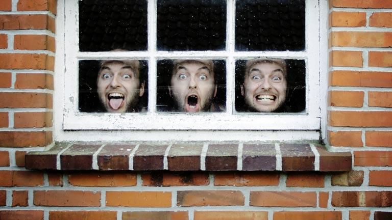 Hinter einem Fenster ziehen drei männliche Gesichter alberne Grimassen.