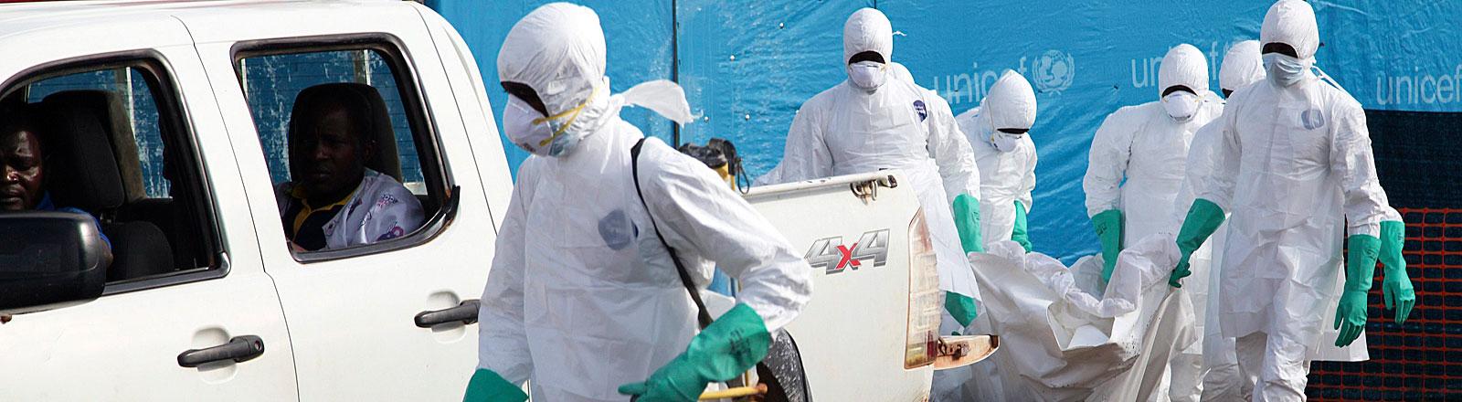 Isolationscamp Foya in Lofa County, Liberia: Hilfskräfte in Schutzkleidung mit einem Ebola-Opfer.