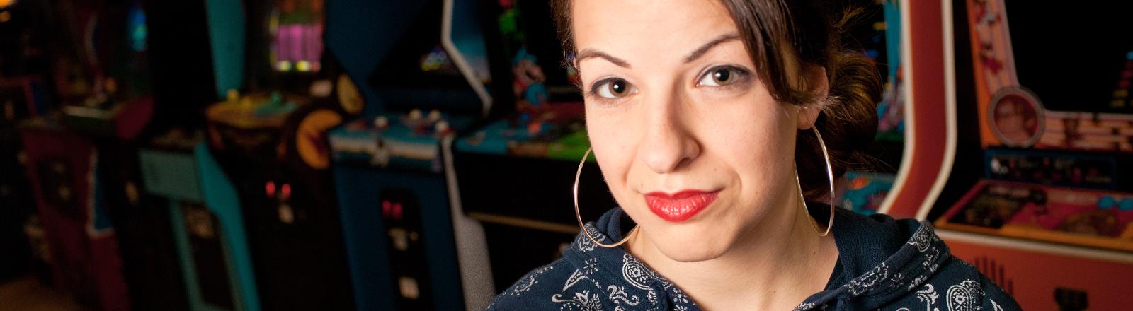 Die Feministin Anita Sarkeesian auf einem Pressefoto vor Spielautomaten.