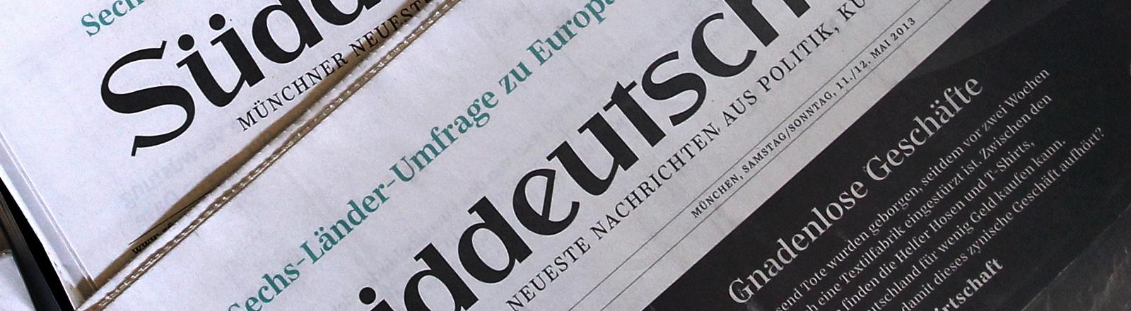 """Ein Stapel der Süddeutschen Zeitung liegt übereinander. Thema im Blatt: """"Gnadenlose Geschäfte""""."""