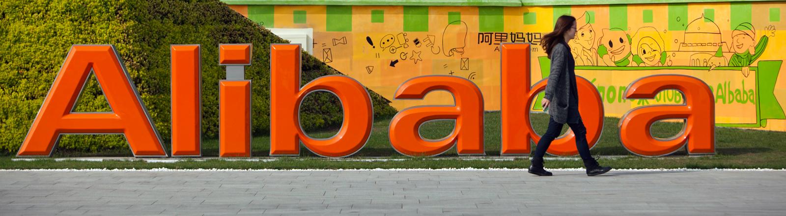 Eine Frau geht am 04.11.2013 am Firmenlogo von Alibaba in der chinesischen Stadt Hangzhou vorbei.