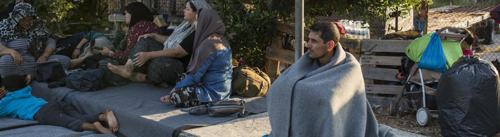 Geflüchtete Menschen sitzen auf der Straße von Lesbos.
