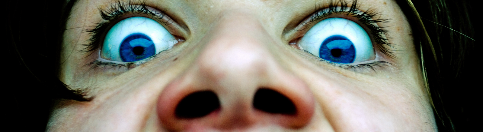 Eine Frau starrt mit weit aufgerissenen Augen über ihre Nase hinweg.