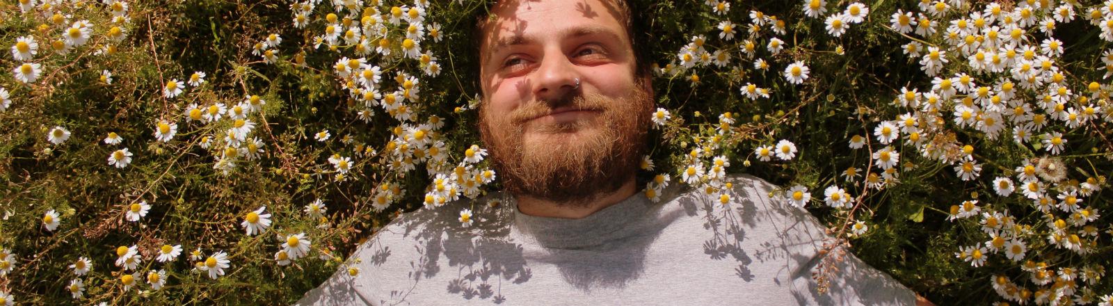 Ein Mann liegt mit breitem Grinsen in einem Feld von Kamillepflanzen.