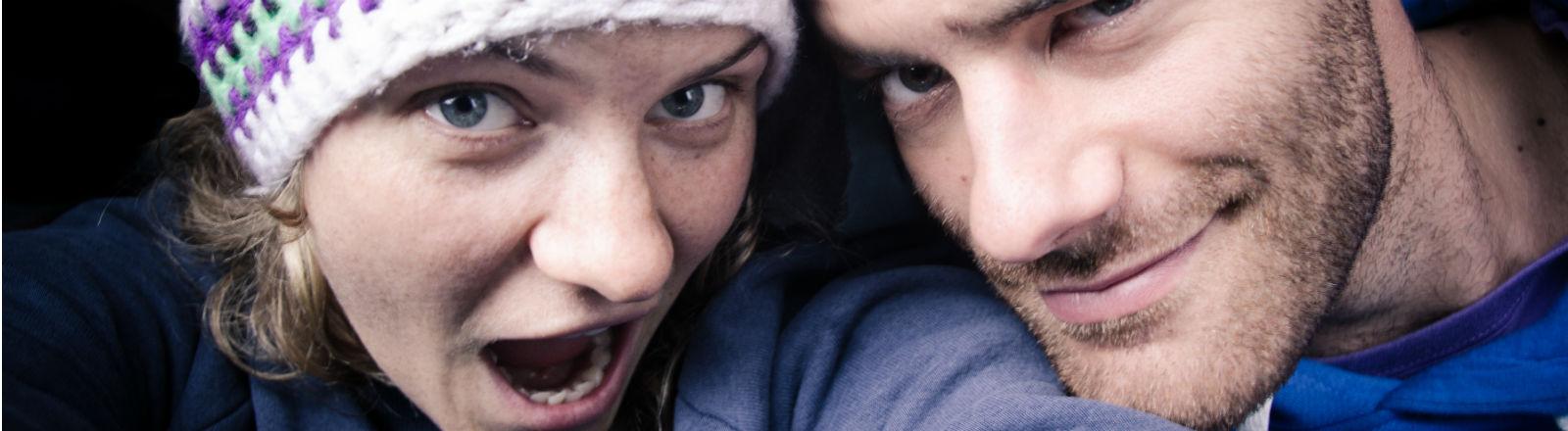 Ein lachendes junges Paar macht ein Foto von sich.