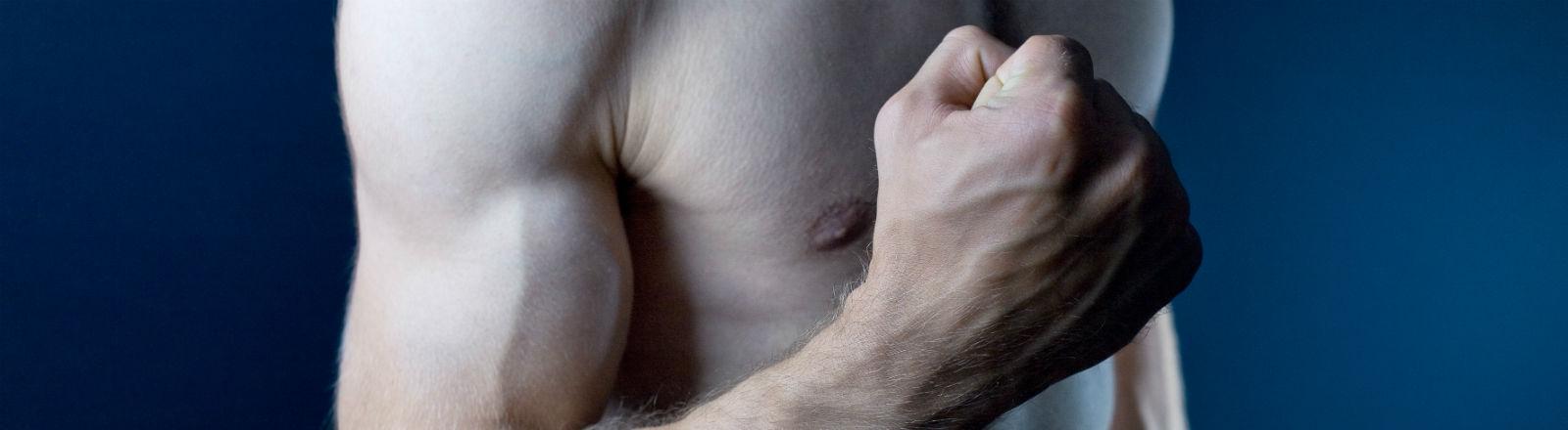 Ein Mann spannt seinen Oberarmmuskel an.