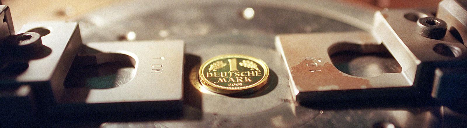 Eine D-Mark-Goldmünze in einer Prägemaschine