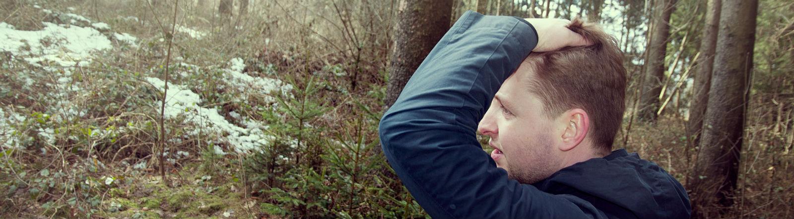 Ein junger Mann steht im Wald und rauft sich die Haare.