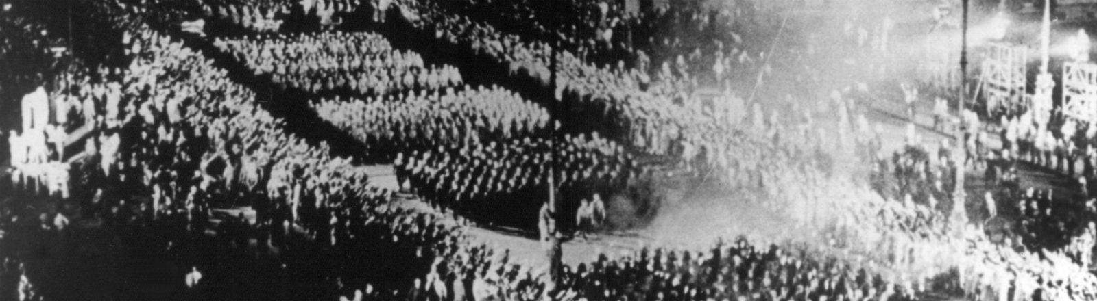 Eine schwarz-weiß Aufnahme, die zeigt, wie die Nazis durch Brandenburger Tor marschieren. Bild: dpa
