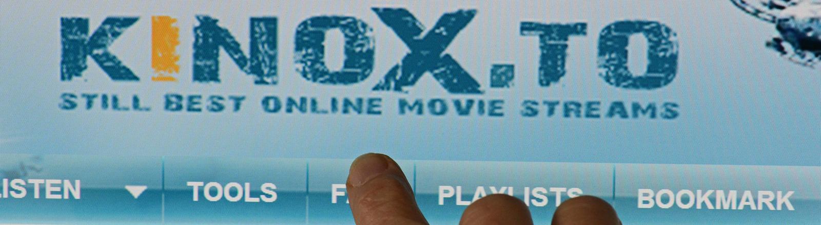 Ein Zeigefinger weist am 26.10.2014 in Dresden (Sachsen) auf die Startseite der Internetplattform Kinox.to.