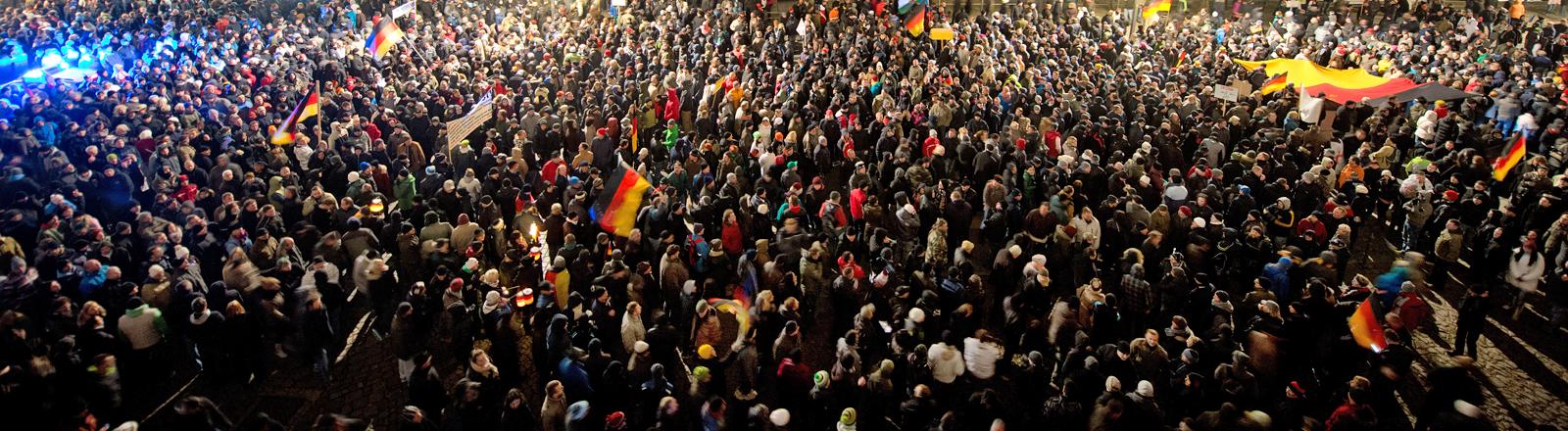 """Teilnehmer einer Demonstration unter dem Motto """"Patriotische Europäer gegen die Islamisierung des Abendlandes"""" (PEGIDA) warten am 01.12.2014 auf dem Terrassenufer in Dresden"""