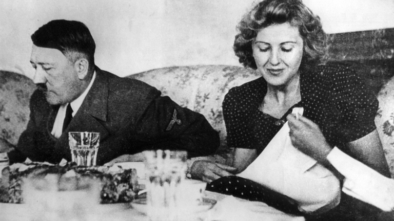Der nationalsozialistische Führer Adolf Hitler mit seiner Lebensgefährtin Eva Braun beim Essen. Undatiert.
