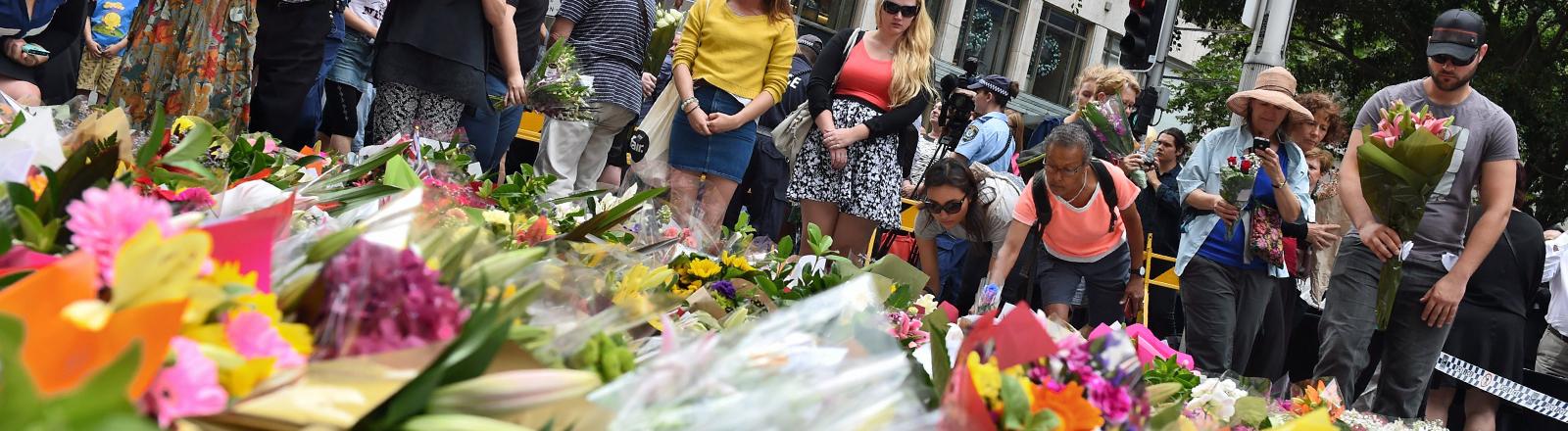 Am 16.12.2014 legen trauernde Menschen in Sydney Blumen nieder, nachdem ein Mann mehrere Geiseln nahm und bei dem Polizeieinsatz er und zwei Geiseln starben.