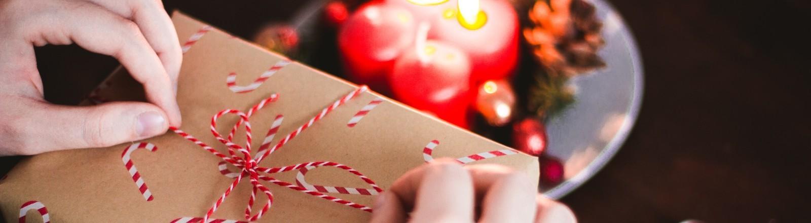 Eine Person verpackt ein Weihnachtsgeschenk an einem Tisch. Davor ist ein Adventskranz.