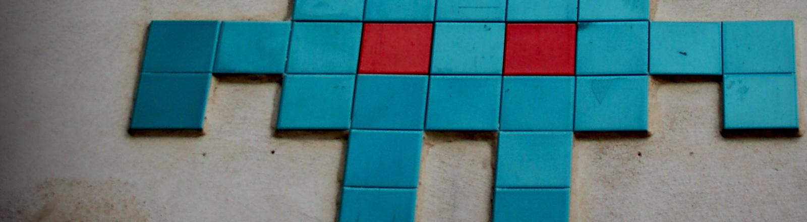 Space-Invaders-Symbol als Mosaik auf einer Hauswand.