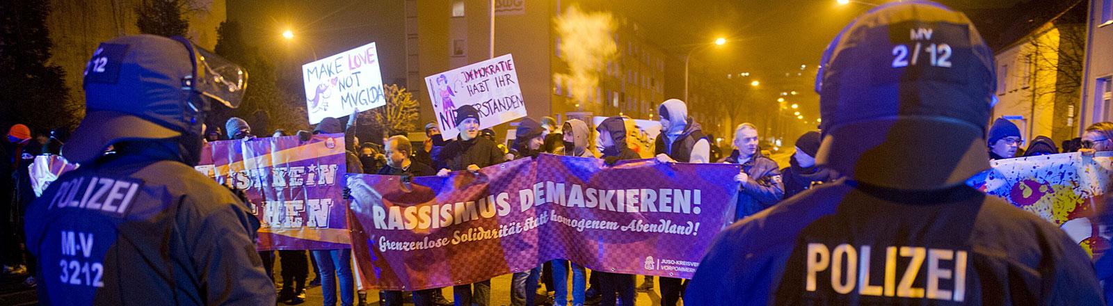 """Gegendemonstranten protestieren am 19.01.2015 mit einem Plakatschriftzug """"Rassismus Demaskieren!"""" gegen die islamkritische Bewegung der Mvgida (Mecklenburg-Vorpommern gegen die Islamisierung des Abendlandes) in Stralsund"""