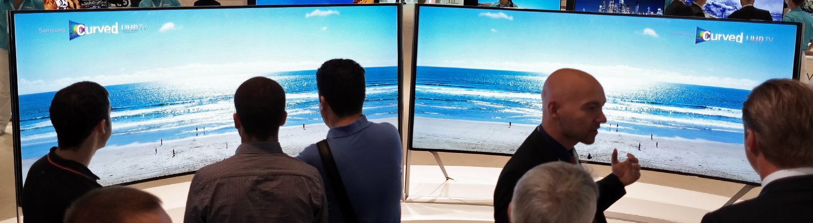 Menschen stehen vor zwei Fernsehern von Samsung und gucken die sich an.