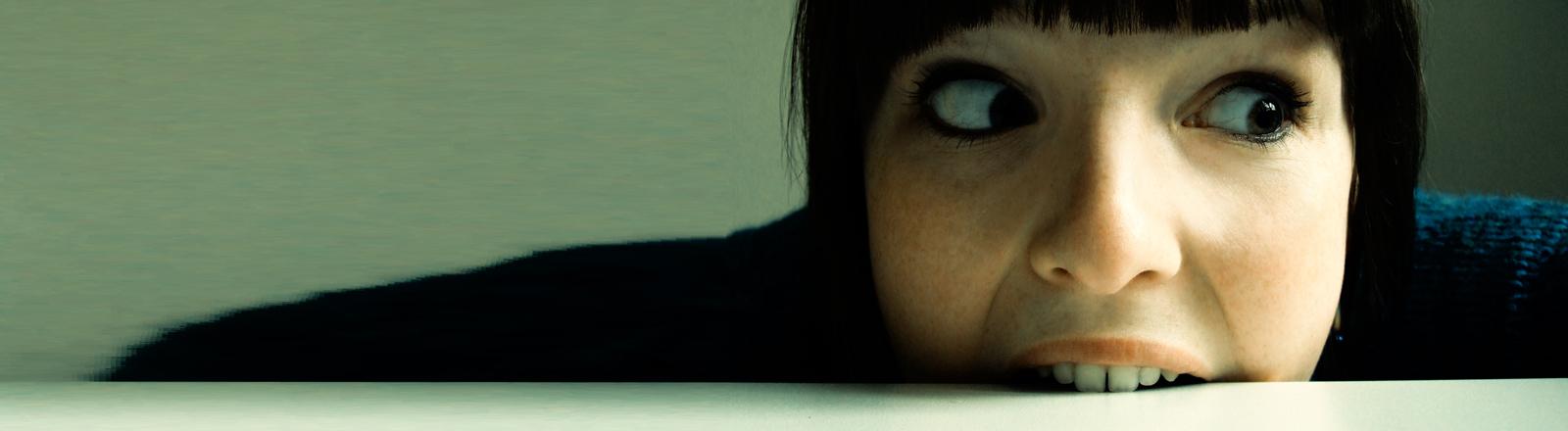 Eine Frau beißt in die Tischkante.
