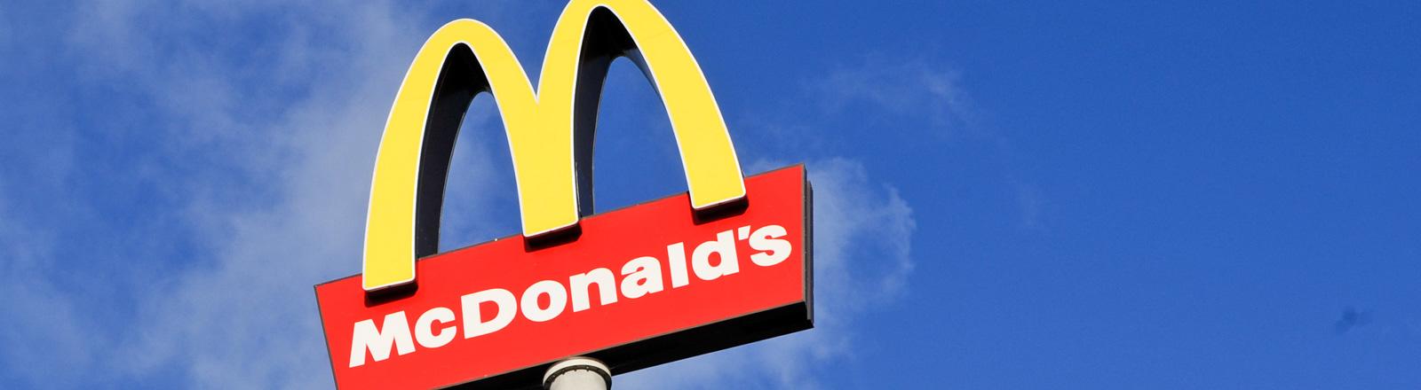 Das Schild der Restaurant-Kette McDonald's vor blauem Himmel. Ein gelbes M. Darunter steht Mc Donald's in weißen Lettern auf rotem Grund.