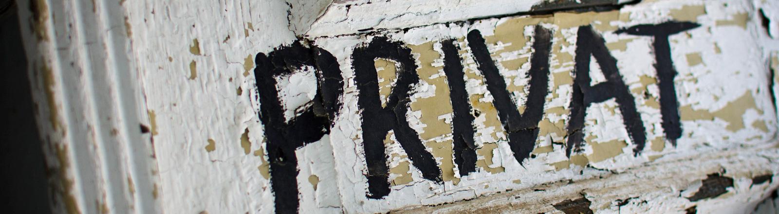 """Auf einer Holztür, von der der weiße Lack abblättert steht """"privat""""."""