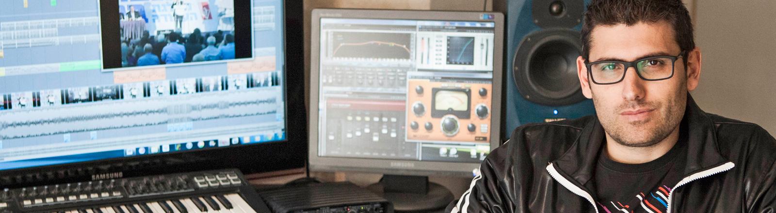 Der Musikkünstler Noy Alooshe sitzt in seinem Studio in Tel Aviv. Er hat kurze schwarze Haare und trägt eine Brille; Bild: dpa