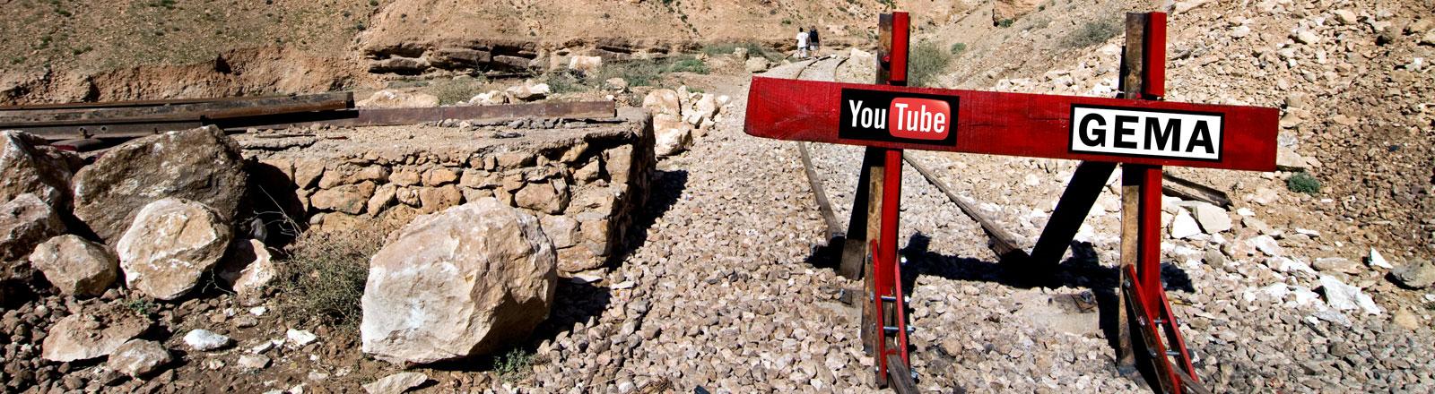 Absperrung in steiniger Gegend mit Logos von YouTube und GEMA (Collage DRadio Wissen)