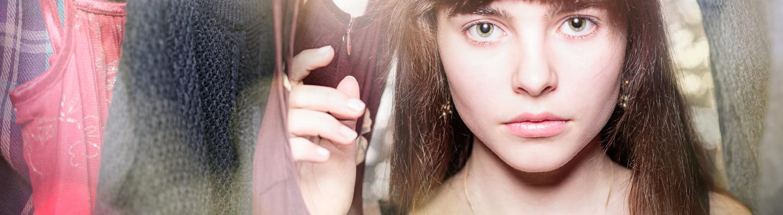Eine junge Frau schaut aus ihrem Kleiderschrank durch ihre Kleider.