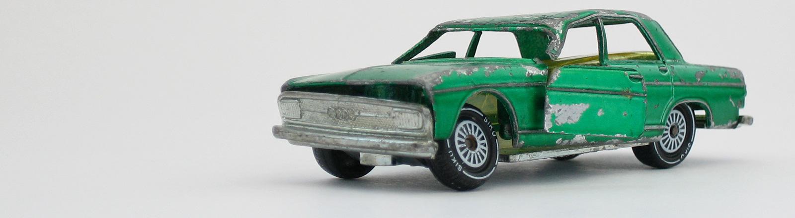 Ein grünes kaputtes Spielzeugauto vor grauem Hintergrund.