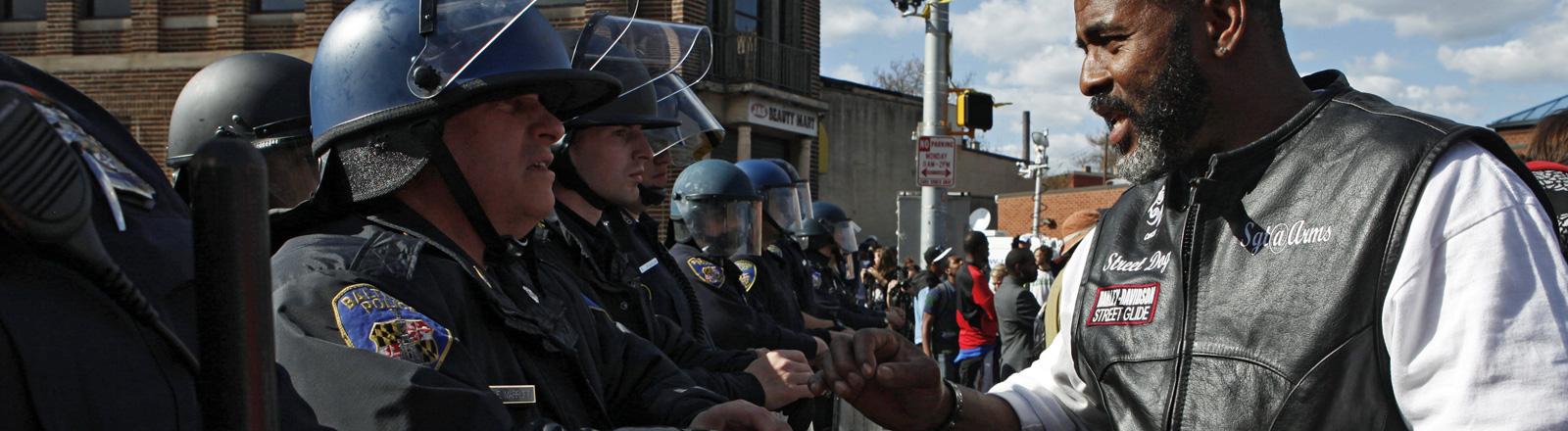 Ein Mann steht vor einer Reihe Polizisten und redet mit einem der Polizisten, Baltimore nach den Krawallen; Bild: dpa