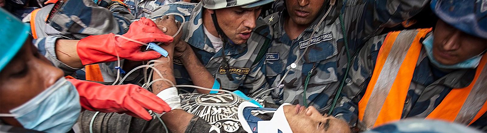 Der 15-jährige Pemba Tamang wird nach dem Beben in Nepal gerettet. Er liegt auf einer Trage. um ihn stehen viele Helfer (30.04.2015); Bilder: dpa