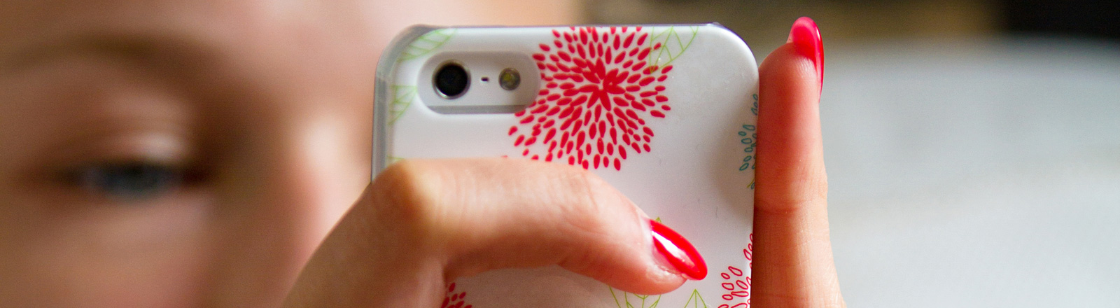 Eine Frau, deren Gesicht unscharf zu sehen ist, hält ein Smartphone in den Händen. Sie hat rot lackierte Fingernägel.